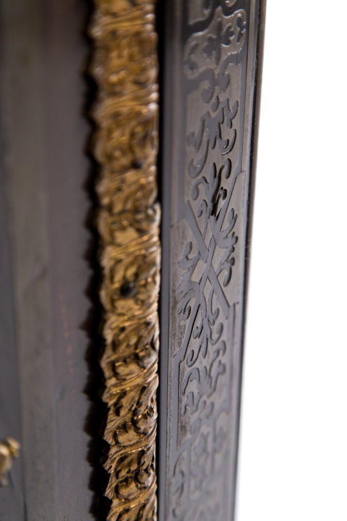 Blistered brass inlay detail requiring consolidation