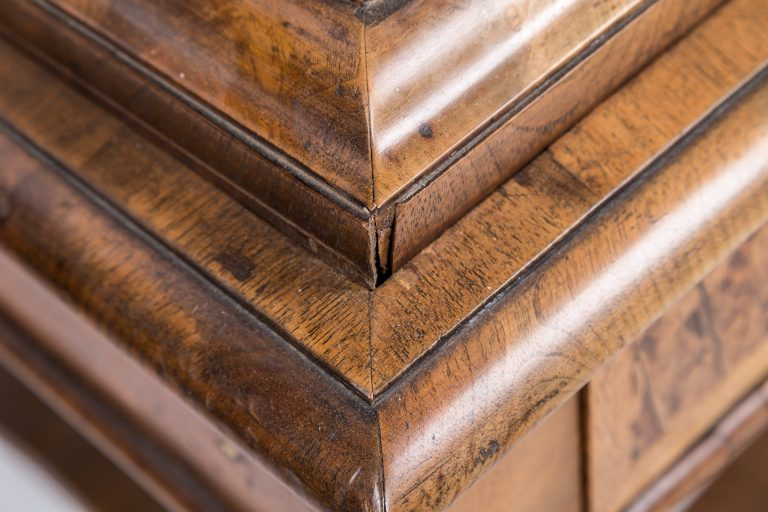 Walnut moulding detail on chest on stand