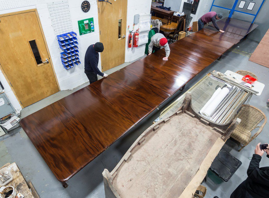 Polishing 32ft long dining table, viewed in the main workshop